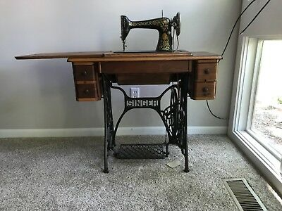 antique Singer treadle sewing machine and cabinet in working condition.