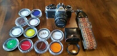 Nikon FE2 35mm SLR camera, 14 lenses and carrying strap.black and silver body