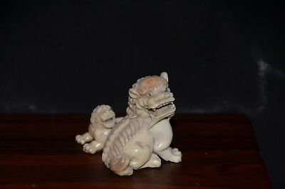Netsuke, Shishi mit Jungem, fossiles Material, sign.