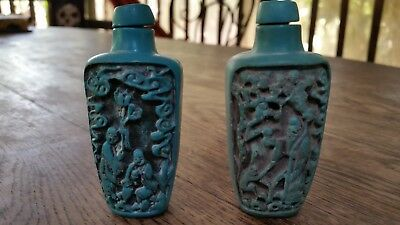 Turquoise colored Chinese snuff bottles pair with hand carved scenes on them.