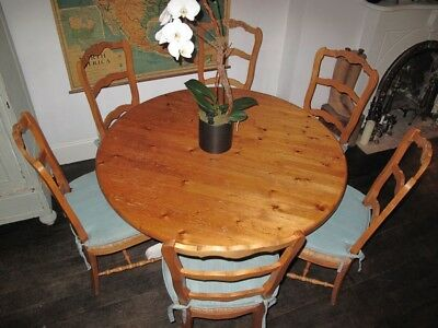 French country dining table, round with six chairs and cushions.