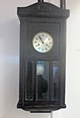 Vintage wall mounted chiming pendulum clock in a wooden case