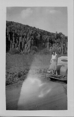 Vintage photo woman standing on the back of her car by rock formation Texas 40's