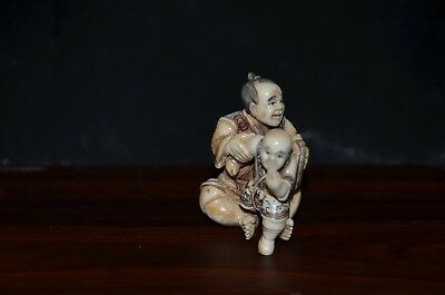 Netsuke, Mann mit Kind, fossiles Material, kol. Sign. 42mm