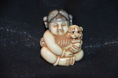 Netsuke, Kind mit Shishi, fossiles Knochenmaterial, Augen Horn, sign. 45mm
