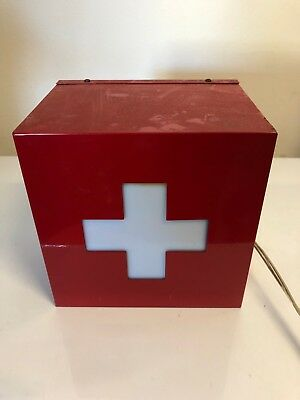 vintage first aid sign that is a red metal box with light up cross
