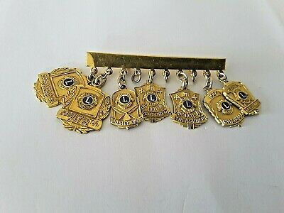 lions club badges  7 gold plated  on bar all good  condition