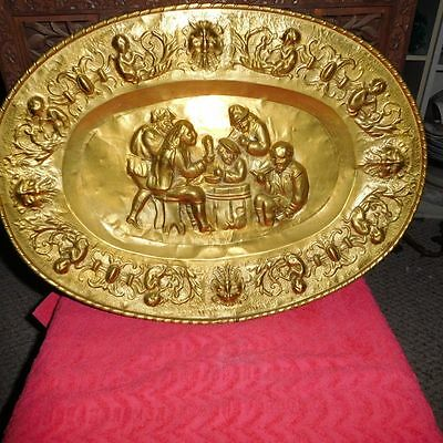 Antique Brass Oval Wall Plate With A Great Design Of 5 Guys Having A Party