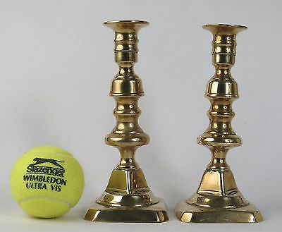 Pair of square based brass candlesticks 18cms high