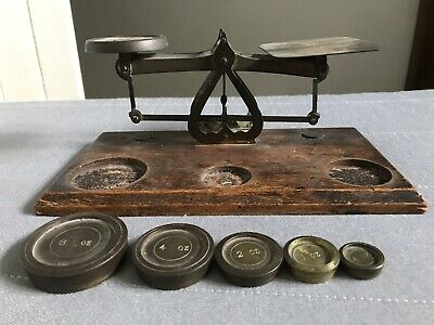 Early 20th century set of brass postal scales and weights on oak base