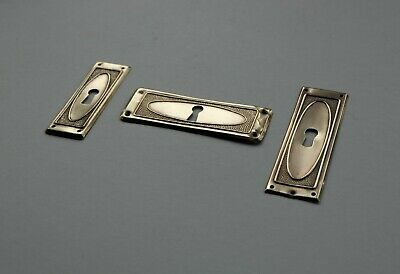 Three stamped brass cabinet furniture drawer or door keyhole escutcheon plates