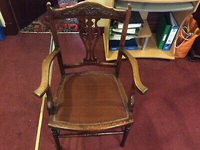 antique wood chair medium brown with ornate carving and red cloth seat