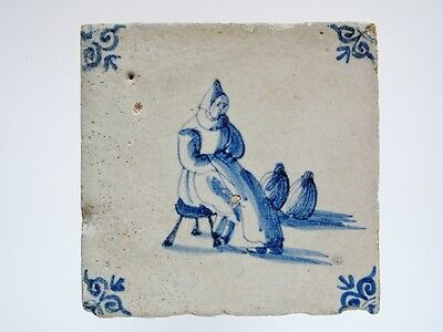 An antique Dutch Delft tile with a saleswoman selling her goods Vermeer....