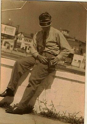 Vintage Antique Photograph Man With Visor Hat and Camera Case Sitting on Wall