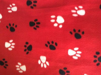 """black and white dog paw prints with red background fleece fabric, 60"""" wide BTY"""