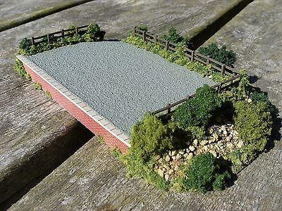 N gauge model railway layout loading platform scenery with fencing and bushes