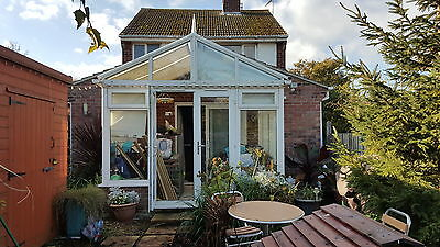 White UPVC Conservatory with blinds and cane furniture
