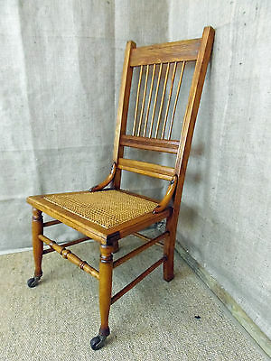 Vintage wooden bedroom chair, cane seat spindle back, low level, with castors.