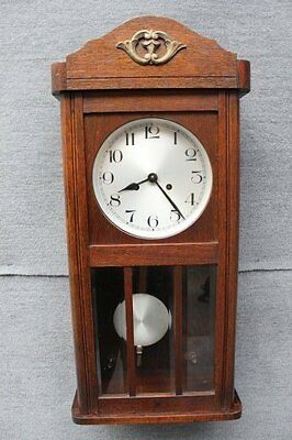 Oak cased wall hanging clock with moving pendant with key bevelled glass front