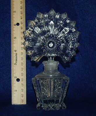 Vintage perfume bottle with clear glass base and ornate ground stopper