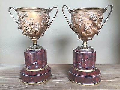 Pair French bronze figural Urns. Cherubs & Satyrs on a base of Rouge marble.