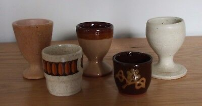 Collection of five stoneware egg cups in a variety of designs