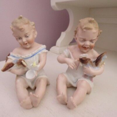 Pair of bisque porcelain piano babies boy & girl feeding chooks Germany