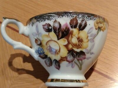 Gold trimmed tea cup with yellow and brown flowers.