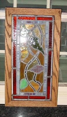 Antique leaded stained glass window in oak frame