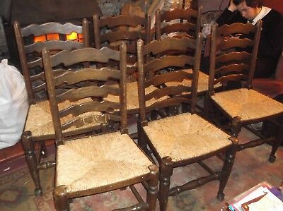 A set of 6 country style rush seated ladder back dining/kitchen chairs.