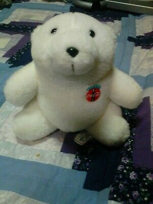 a white Coca-Cola bear with a pin that says always Coca-Cola