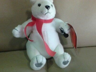 a white Coca-Cola bear with scarf and Coca-Cola bottle