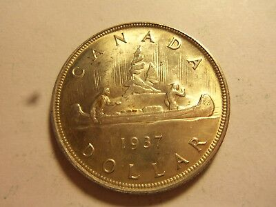 1937 toned  canadian silver dollar unc.