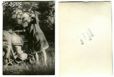 Vintage Photo 1960s young woman on motorcycle looking at the rearview mirror