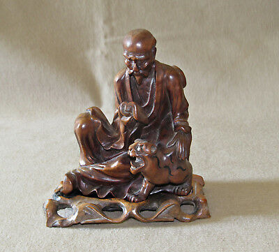 Finely carved Japanese wooden figure of scholar and tiger, on stand