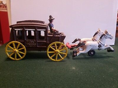 Vintage cast iron Wells Fargo stagecoach, two white horses, and driver
