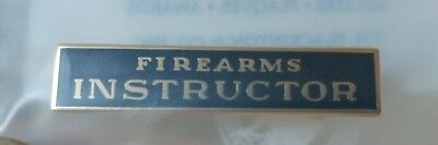 New Firearms Instructor pin with black background and gold writing.