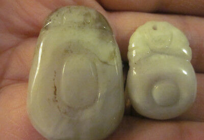 2 small carved light green hard stone Asian pendants oval shapes