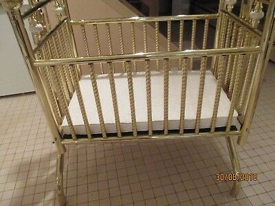 brass swinging crib with fluted spindles on crib
