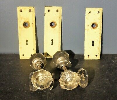 Three sets of antique glass door knobs and three rectangular backplates