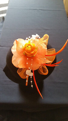 Fascinator - Pale orange sinamay with flower, feathers & beads mounted on band