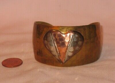 A Vintage Hammered Brass Cuff Bracelet With A Raised Silver And Copper Heart