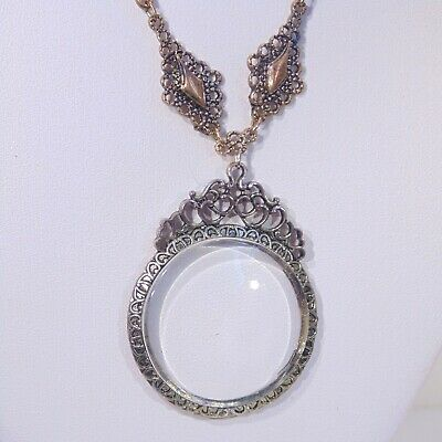 Magnifying glass pendant necklace, ornate filigree details, copper/brass tone