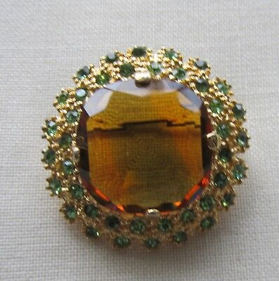 Vintage gold tone flower brooch with brown and green rhinestones