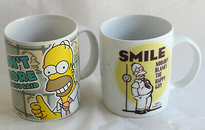 """2x Simpsons Coffee Mug """"Smile Nobody ..."""" 2011 """"I Couldn't Agree More..."""" 2010"""