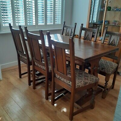 Old Charm oak extending dining table and six carved oak chairs