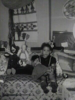 Segregation African American  Girl holding a colored doll white doll on couch