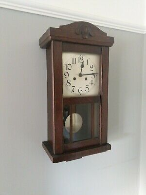 Vintage wall clock in wooden case with pendulum