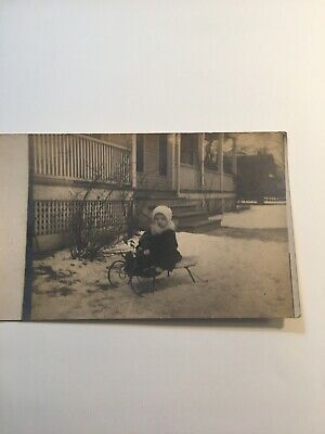Antique RPPC Real Photo Postcard of Child on Sled Holding Teddy Bear Posted 1910