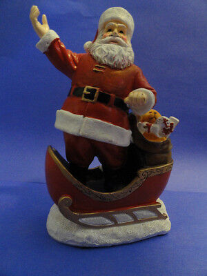 Santa Claus figurine in sleigh with bag of toys